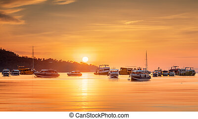 sunrise with colorful sky and boats on the beach - Beautiful...