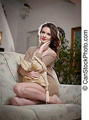 Young sensual woman sitting on sofa relaxing Beautiful long...