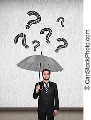 falling question mark - young businessman holding umbrella...