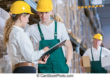 Manager talking with storage worker in warehouse