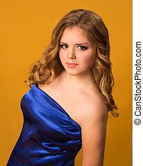 Lady in blue dress with big eyes on orange background