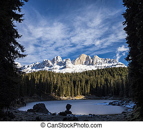 Carezza lake in winter with frosty surface In the background...