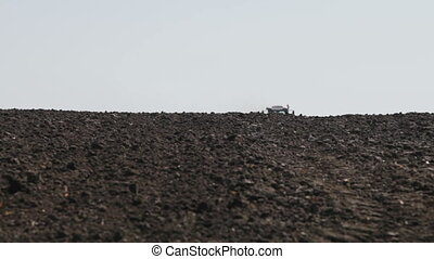 tractor leaves the horizon plowed field and birds flying...