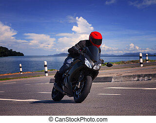 young biker man riding motorcycle on asphalt road against...