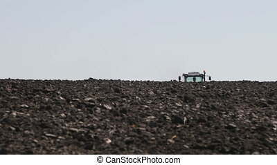 tractor plowing the black earth ground leaves the horizon...