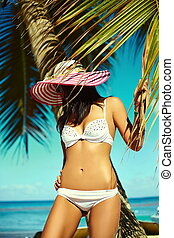High fashion look.glamor sexy sunbathed model girl in white lingerie bikini in colorful sunhat behind blue beach ocean water near tropic palms