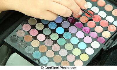 Woman using palette with eye shadow and glossy lipstick,...
