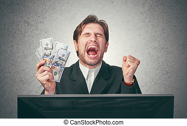 happy businessman with money in hand and computer rejoices...