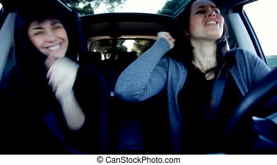 Two beautiful happy women dancing while driving - Funny...