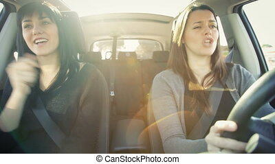 Two happy female friends driving - Funny women driving car...