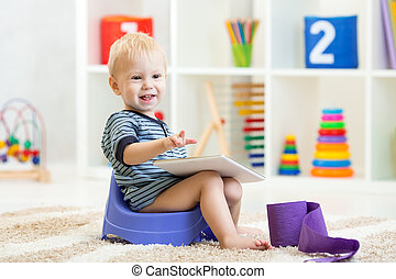 smiling child sitting on chamber pot indoors