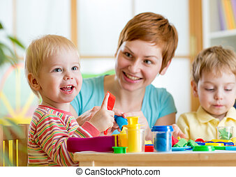 woman playing and teaching with children - woman teaches...