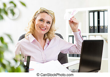businesswoman throwing paper airplane in office - mature...