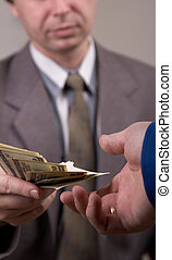 Giving the Money - Businessman in suit giving dollars to...