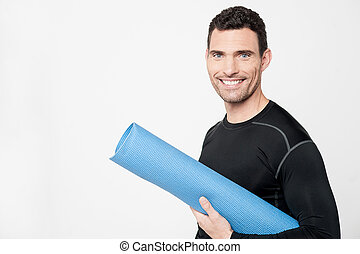 Gym instructor holding mat - Fitness male with rolled up...