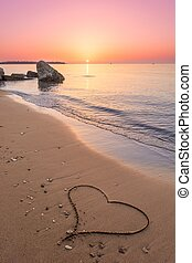Heart drawn on the beach sand with sun above the horizon