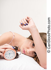 beauty lying on the bed with clock