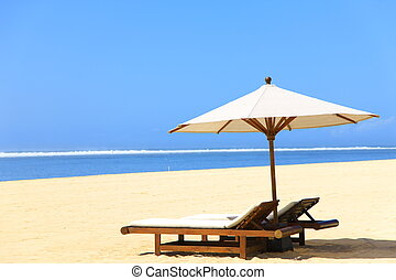 beach resort - long chair and parasol at the beach of tropic...