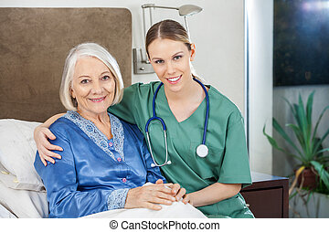 Happy Caretaker With Arm Around Senior Woman At Nursing Home...