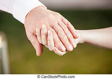 Nurse Holding Senior Man's Hand - Cropped image of female...