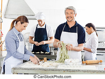 Smiling Male Chef With Colleagues Preparing Pasta In Kitchen...