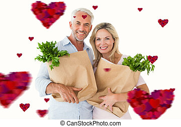 Composite image of happy couple carrying paper grocery bags...
