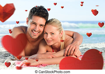 Composite image of lovers lying down on the beach - Lovers...