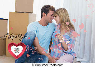 Composite image of couple holding new house key against cardboar