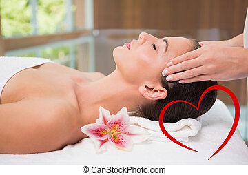 Composite image of attractive woman receiving head massage at sp