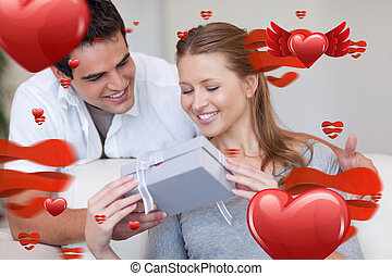 Composite image of woman opening the gift she got from her boyfr