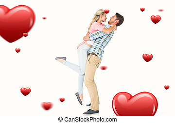 Composite image of handsome man picking up and hugging his...