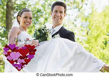 Composite image of groom carrying bride in garden - Groom...