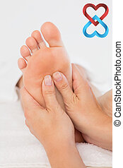 Composite image of close-up of a woman receiving foot...
