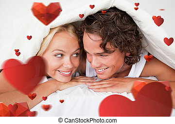 Composite image of couple under a duvet with a knowing smile...