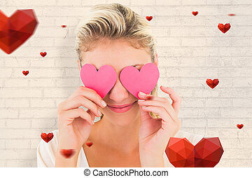 Composite image of attractive young blonde holding hearts...