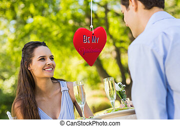 Composite image of couple with champagne flutes sitting at...