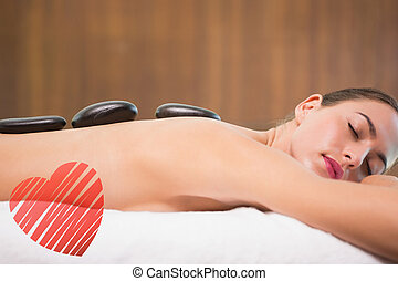 Composite image of beautiful woman receiving stone massage...