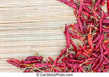 Dried red hot peppers on traditional mat, with copyspace on...
