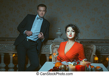 Woman sitting, man standing out of focus. - Woman in red...