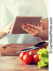 closeup of man pointing finger to tablet pc - cooking,...
