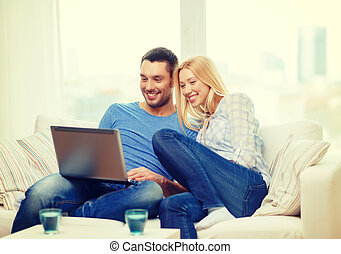 smiling happy couple with laptop at home - love, family,...