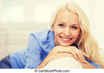 smiling young woman lying on sofa at home - home and...