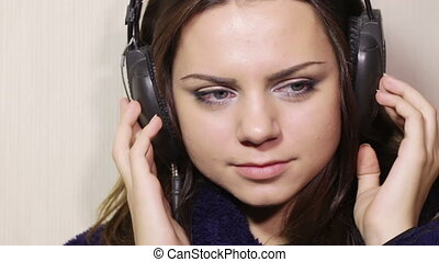 Girl bathrobe with headphones CU - Seated in the headphones...