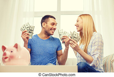 couple with money and piggybank ot table at home - love,...