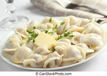 Ravioli - Pelmeni with butter and parsley closeup