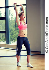 smiling woman with expander in gym - fitness, sport, people...