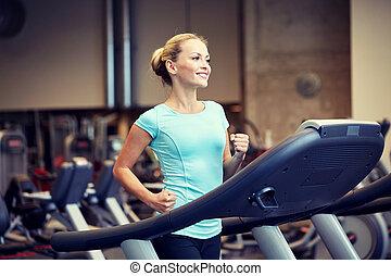 sonriente, mujer, ejercitar, en, noria, en, gimnasio,