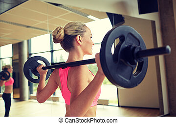 sporty woman exercising with barbell in gym - fitness,...