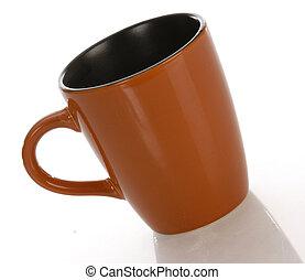 orange and black coffee mug with reflection on white background