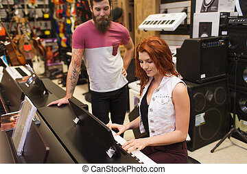 man and woman playing piano at music store - music, sale,...